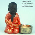 Resin baby monk statue with candle holder.