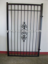 Black ornamental iron gate with top and bottom bars and decorative scrolls.