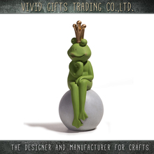 Ceramic frog with gold crown sitting on ball for home and garden decoration