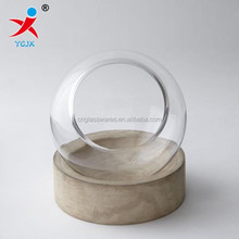 round glass terrarium with wooden base