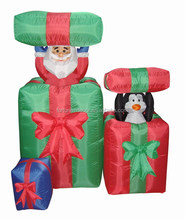 150cm/5ft inflatable santa claus and penguin on the up and down gift bag behind a small git bag