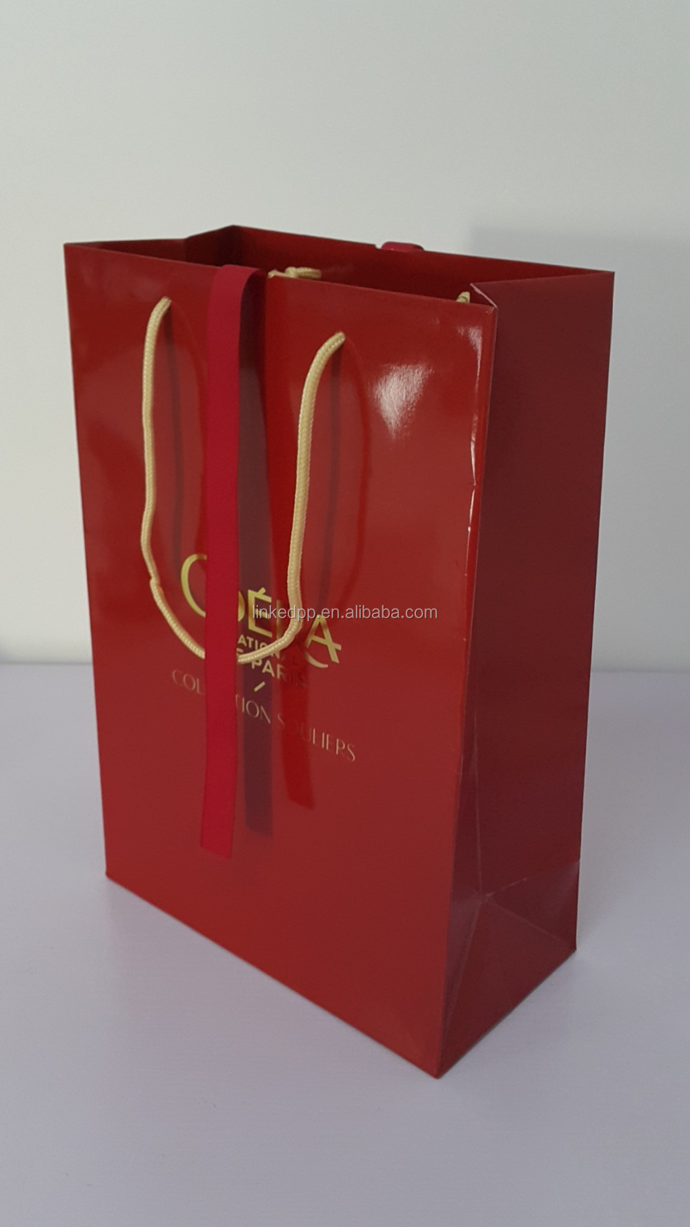 Glossy paper gift bag with rope handle and ribbon bow tie