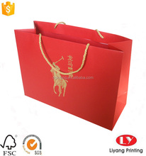 Large red paper shopping bag with gold rope handle