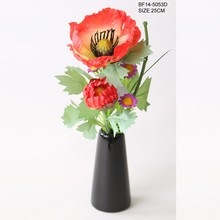 Red artificial poppy with two heads in black vase
