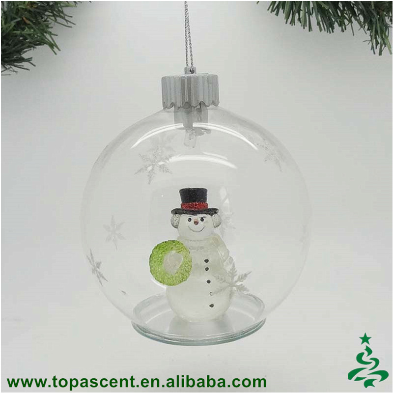 Traditional hand blown glass clear dome with snowman holding garland inside ornament for christmas decoration