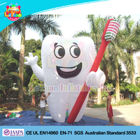 Inflatable tooth with toothbrush on hand for dentist's advertising