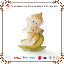 Polyresin small baby angel figurine sitting on fruits