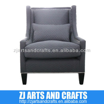 0473 arm sofa (Quilted charcoal linen arm chairr. With silver studs around arms and base with wenge finished legs.)
