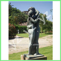 nude man and woman kissing garden statue