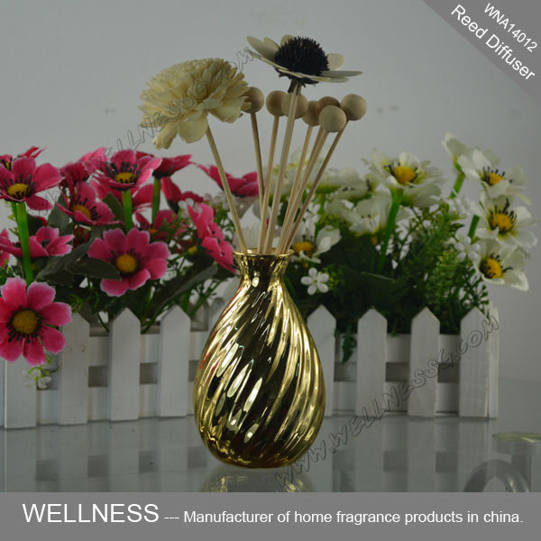 reed diffuser with rattan sticks and sola flower in golden bottle