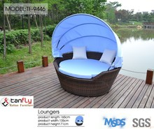 Double seat rattan lounge chair with umbrella.
