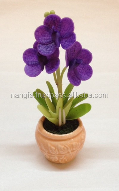 Miniature clay flower in ceramic base