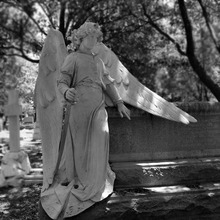 Stone female angel statue standing beside the grave marble cemetery sculpture