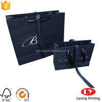 Elegante matte black paper gift bag with silver logo and ribbon bow tie closure