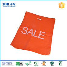 Solid orange color plastic bag carrying handle die cut recyclable bag