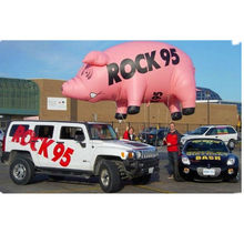 Giant inflatable pig flying helium balloons