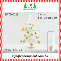 Set of gold and silver hanging balls and white artificial christmas tree