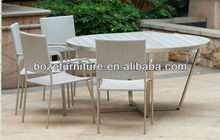 stainless steel rattan stacking chair and round wooden table used in restaurant