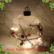 Clear glass snow ball with red fruit ornaments