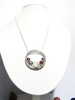 Silver pendant set with one moon stone and four garnets