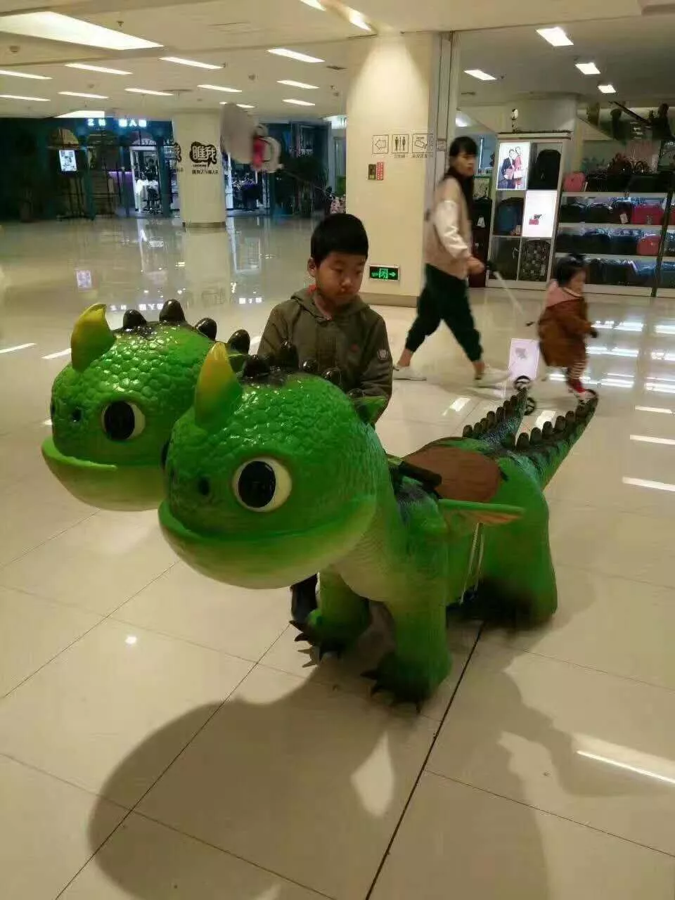 Attractive kids playing dinosaur ride walking animal with handmade realistic skin