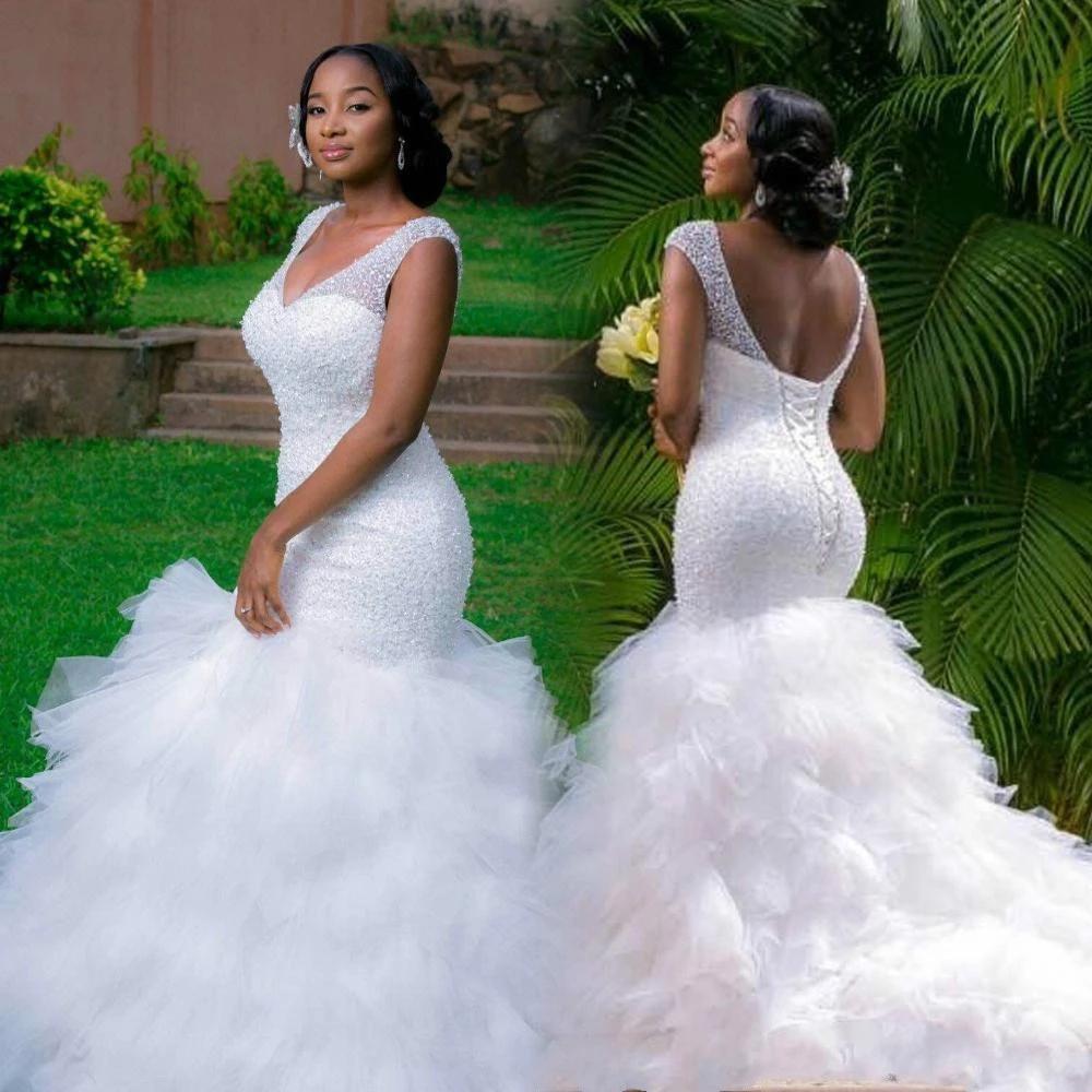Alibaba.com / Customize Latest African Bridal Sexy V Neck Sleeveless Sequins Bust Ruffles Skirt Long Train Mermaid wedding dress