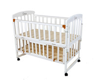 White wooden baby crib with wheels