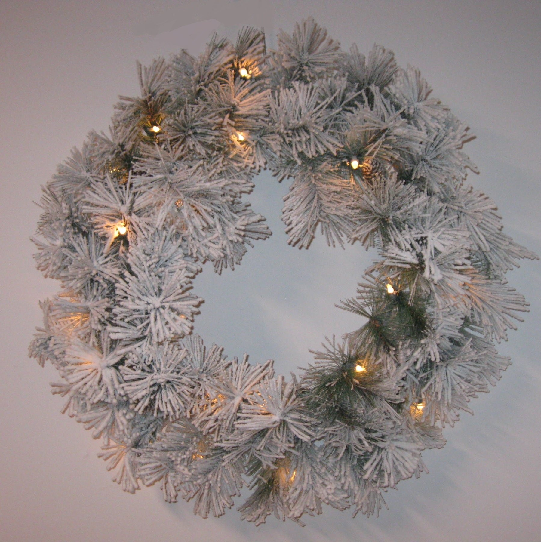 lighted christmas snow flocked wreath with pine branches with pinecone accents
