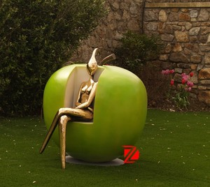 Bronze abstract lady sitting in apple chair sculptures in garden