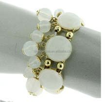 Stretchable bracelet with round stones set around the band. Smaller sphere beads hang down from the main band