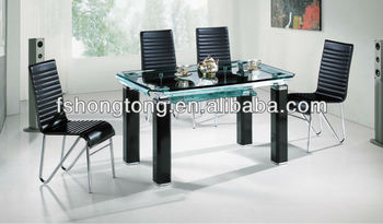mesa de vidrio con sillas negras