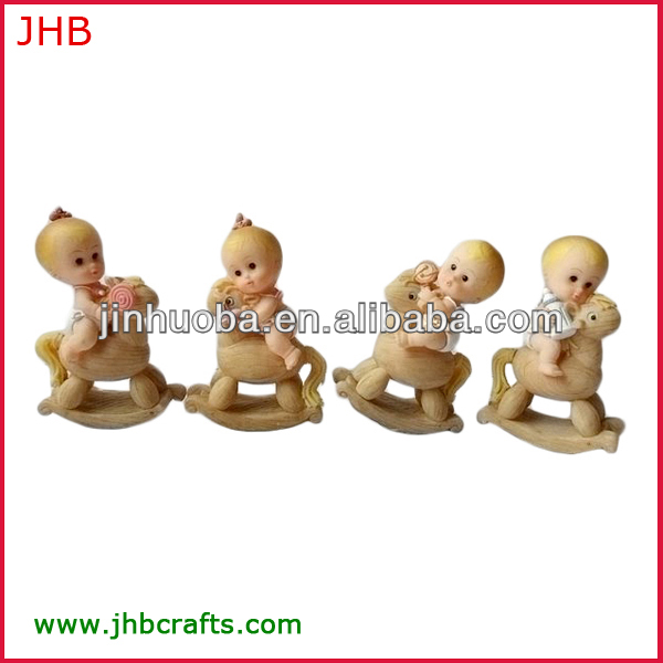 Baby figurine sitting on rocking horse