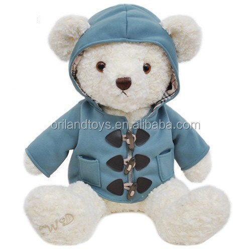 curly plush white teddy bear in blue jacket clothes with embroidery in feet