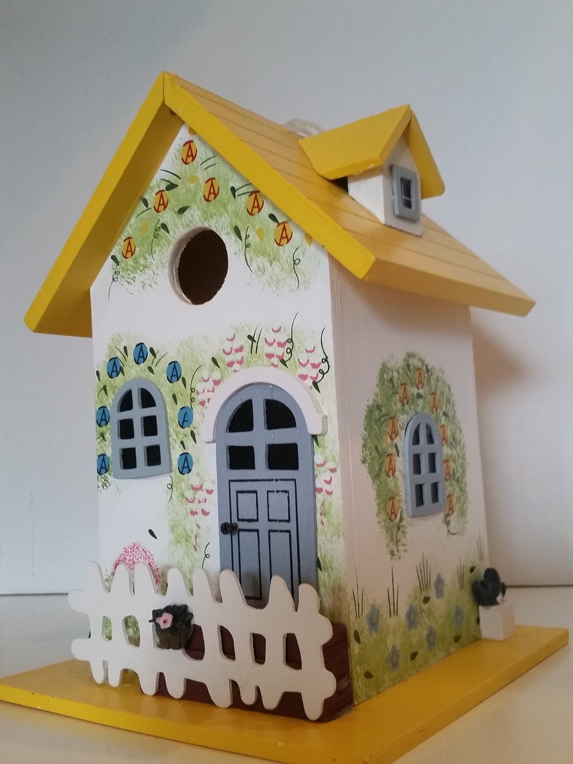 Garden Cottage Birdhouse is decorated to compliment any patio garden this Wood Birdhouse is hand painted with a Colorful Floral Print and a White Pickett Fence