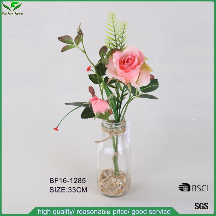 artificial pink rose branch with glass bottle