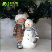 10 in.H standing child statue with white snowman and metal scarf