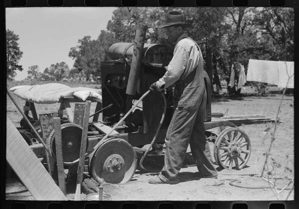 Farmer drilling water well. In this picture he is loosening and tightening rope around the pulley, thus raising and lowering the drilling tool. Pie Town, New Mexico