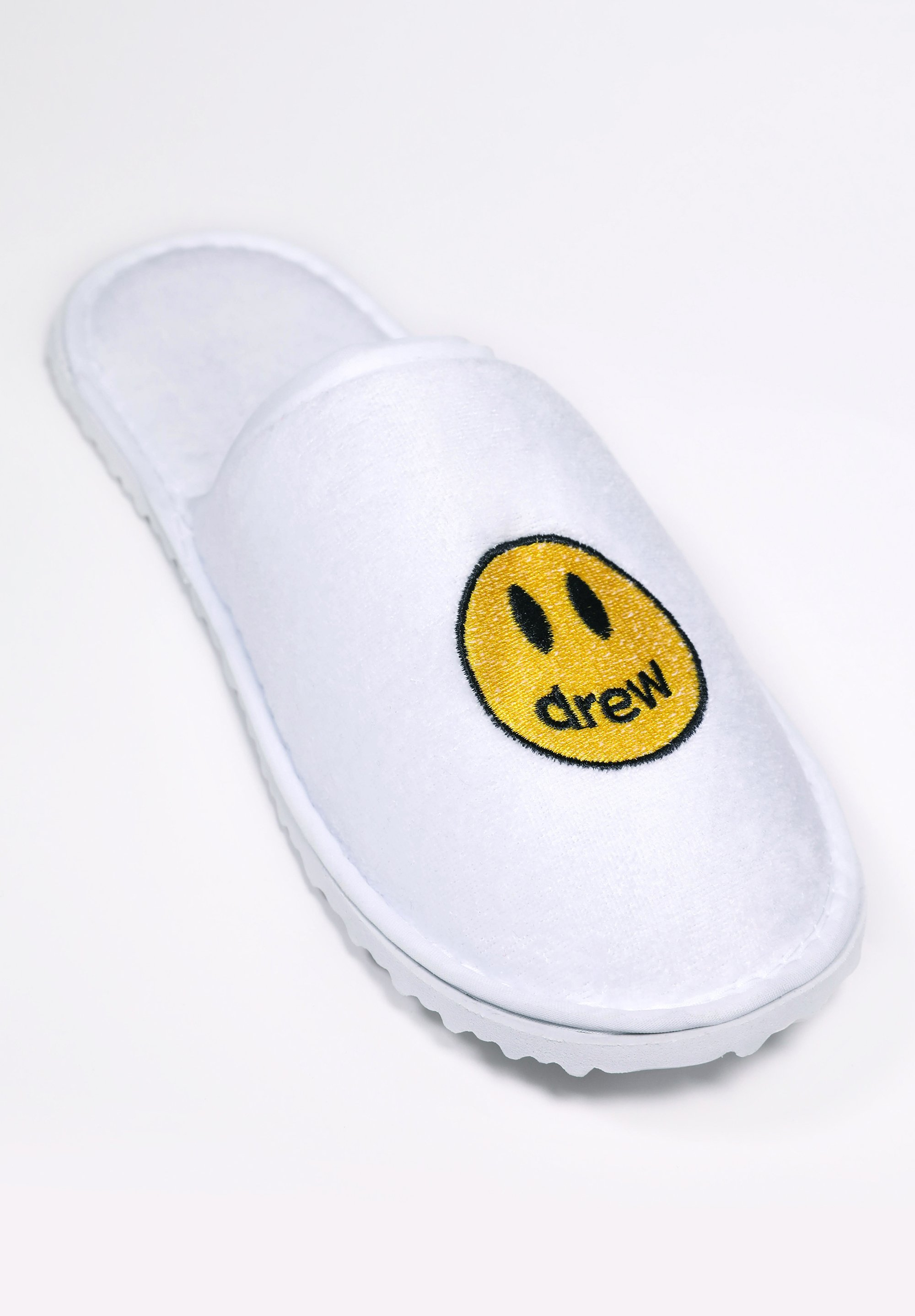 white velour hotel slippers with smile face
