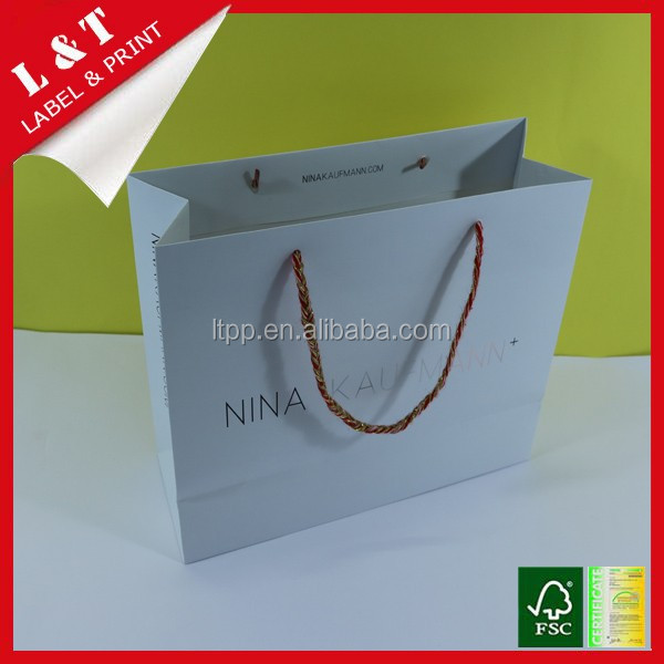 White graceful shopping paper bag with colorful twisted handle