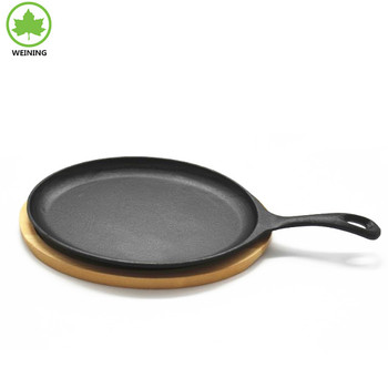 CAST IRON FRY PAN WITH HANDLE ON WOOD BOARD