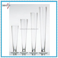 trumpet shaped tall clear flower arrangements in small round glass vases